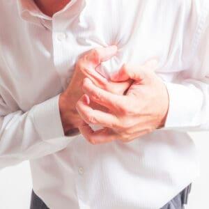 גבר בחולצה לבנה אוחז בלב ונאנק מכאב